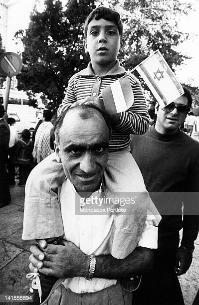 An Isreali man with a child on his shoulders demonstrates for peace in front of the hotel hosting Egyptian president Anwar Sadat Jerusalem November...