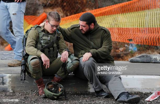 TOPSHOT An Isreali soldier is consoled as Israeli forces and forensic experts inspect the site of a Palestinian driveby shooting attack outside the...