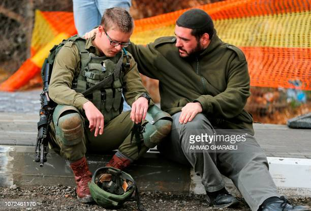 An Isreali soldier is consoled as Israeli forces and forensic experts inspect the site of a Palestinian driveby shooting attack outside the West Bank...