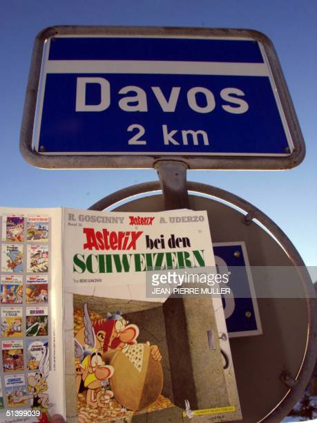 An issue of a worldknown French comics entitled ' Asterix with the Swiss ' by Rene Goscinny and Albert Uderzo hangs by a steetsign pointing at Davos...
