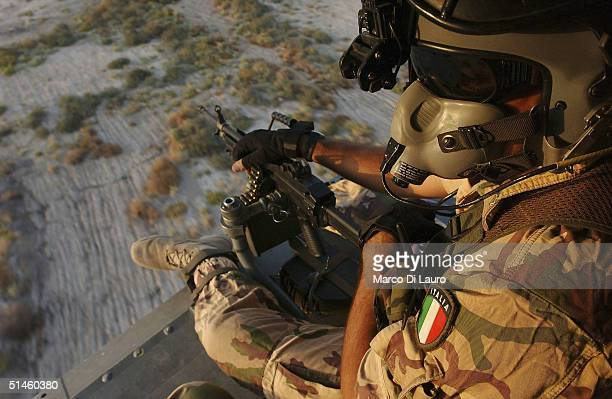 An Italian Air Force gunner from the Italian Joint Task Force Iraq, 6? ROA sits poised with his machine gun as he flyes on a HH-3F helicopter near...