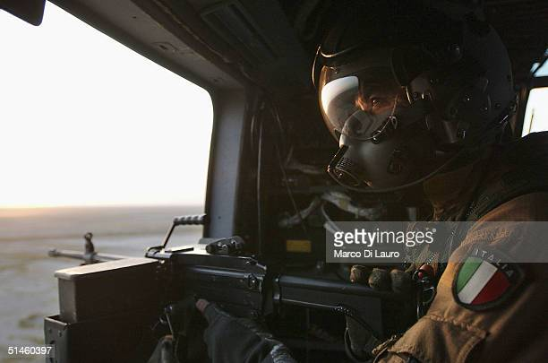 An Italian Air Force gunner from the Italian Joint Task Force Iraq, 6? ROA sits poised with his machine gun as he flys on a HH-3F helicopter near his...
