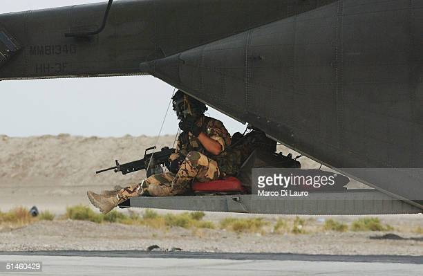 An Italian Air Force gunner from the Italian Joint Task Force Iraq, 6? ROA, sits poised with his machine gun as he flys on a HH-3F helicopter near...