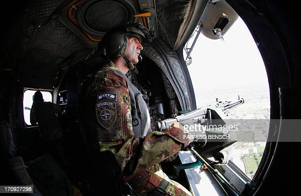 An Italian airforce gunner of the International Security Assistance Force mans his weapon in a CH47 Chinook during a flight over Herat Afghanistan on...