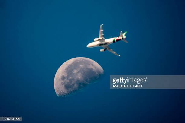 An Italian Alitalia aeroplane flies with the moon in the background over the sky of the capital Rome on August 3 2018