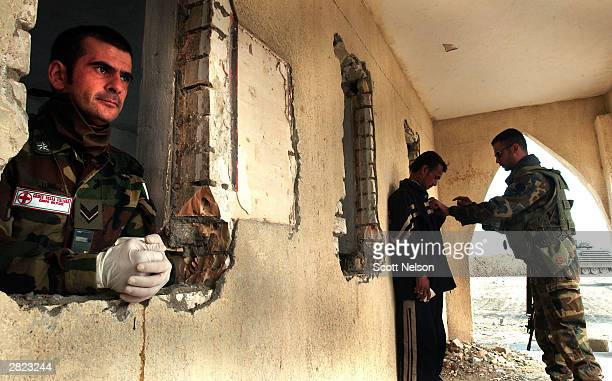 An Italian army dcotor looks on as another soldier positions an Iraqi applicant for the Iraqi Civil Defense Corps for a identification photograph...