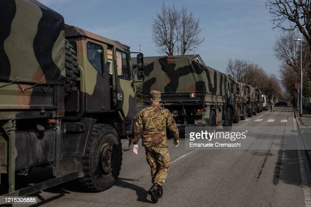 An Italian Army officer walks past a convoy of military vehicles as he takes part to an operation to transport coffins on March 28, 2020 in Ponte San...