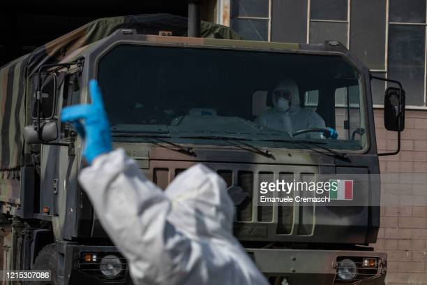 An Italian Army officer, wearing a protective suit, gestures towards an other officer driving a military truck as they take part to an operation to...
