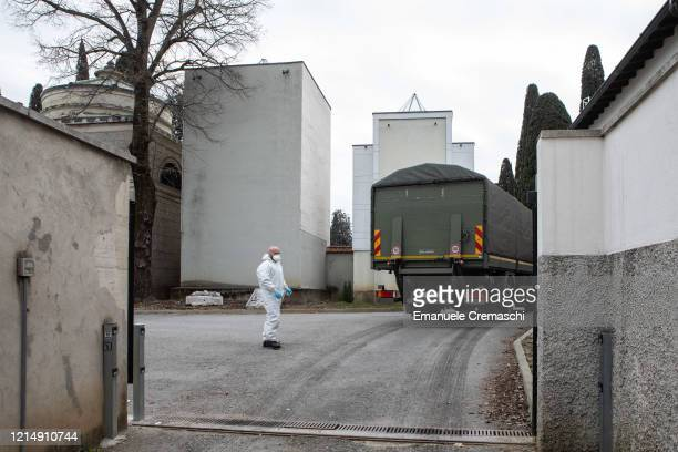 An Italian Army officer wearing a protective suit stands as a military vehicle drives in the Monumental Cemetery on March 26 2020 in Bergamo near...