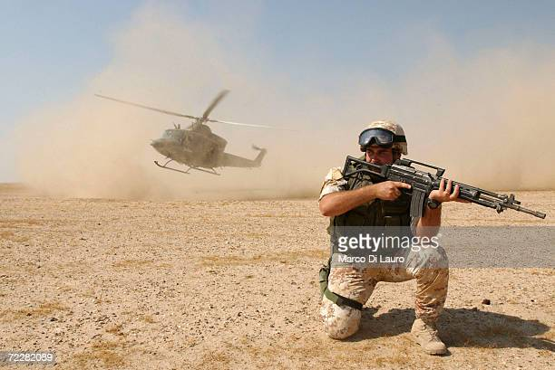 An Italian Army soldier from the Friuli Brigade of the Italian Joint task force Iraq protects an Italian Army AB-412 helicopter as it lands in the...