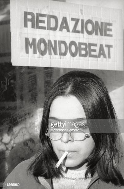 An Italian beatnik smoking under a sign of 'Mondo Beat' magazine 1960s