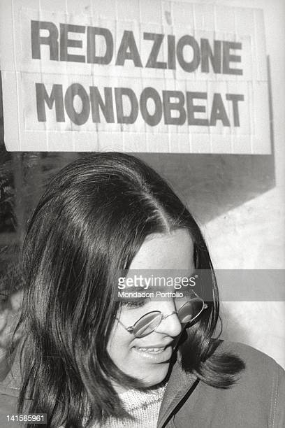 An Italian beatnik standing under a sign of 'Mondo Beat' magazine 1960s