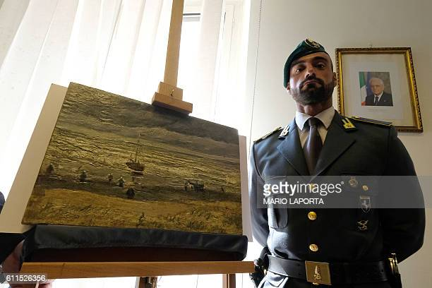 An Italian Border policeman stands next to one of two recently recovered stolen paintings by late Dutch artist Vincent Van Gogh entitled 'The Beach...