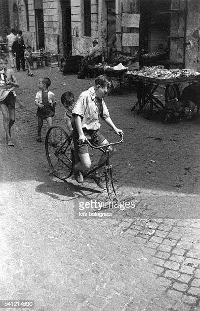 An Italian boy plays on a bicycle without a front wheel in the street