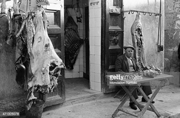 An Italian butcher sitting at the entrance of his shop between the carcasses of a veal and a pig Agrigento 1950s