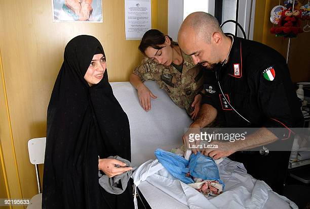 An Italian Carabiniere doctor supported by an Italian female paratrooper of the Folgore Parachute Brigade treats an Iranian child and his mother at...