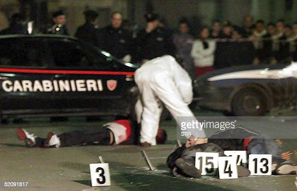 An Italian Carabiniere of the scientific unit, examine bullet-riddled bodies of the three victims, aged between 23 and 25, which were founded dumped...