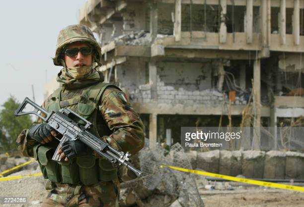 An Italian Carabinieri stands guard outside the rubble of thethe Italian military police headquarters on November 13 2003 in Nasiriyah Iraq A tanker...