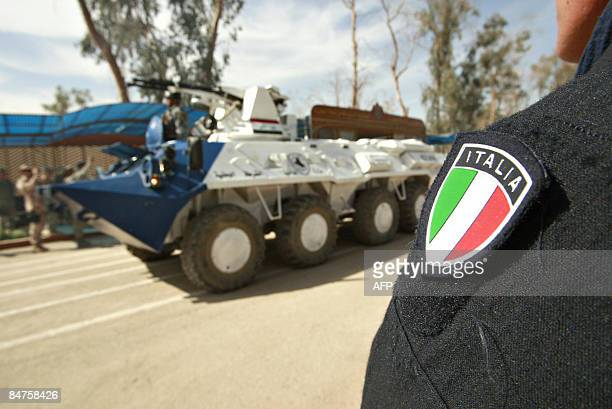 An Italian Carabinieri watches as Iraqi police parade during their graduation ceremony at Camp Dublin inside the Victory Base complex close to...