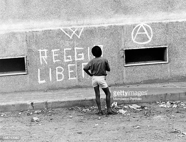 An Italian child observing an anarchical writing on the wall of a building In the city there's a revolt for the choice of regional capital Reggio di...