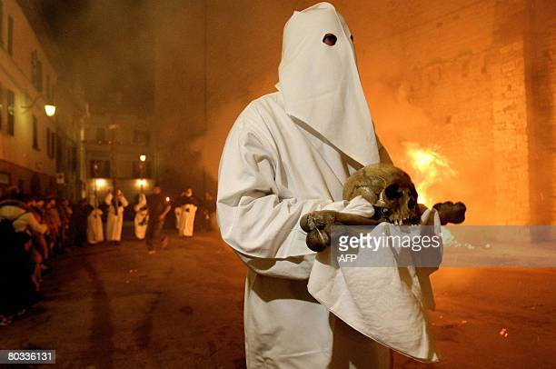An Italian Christian in long hooded robe carries a cross during the Good Friday procession through the streets of Gubbio Umbria on March 21 2008 The...