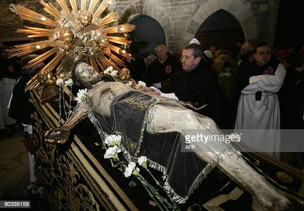 An Italian Christian touches the statue of Jesus Christ on a cross during the Good Friday procession through the streets of Gubbio Umbria on March 21...