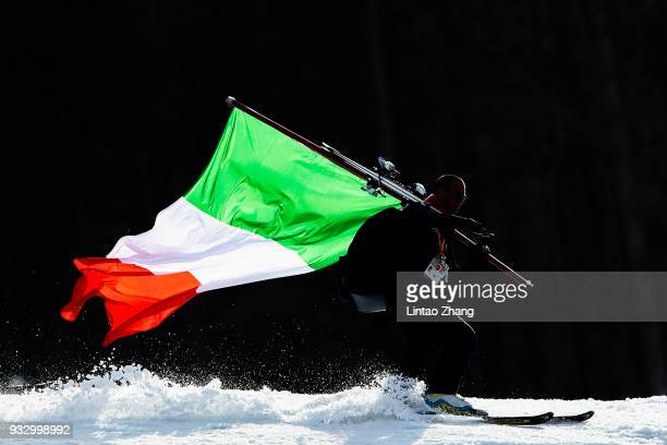 An Italian coach carrying a national flag during the Men's Slalom Run 2 Standing at Alpine Centre during day eight of the PyeongChang 2018 Paralympic...