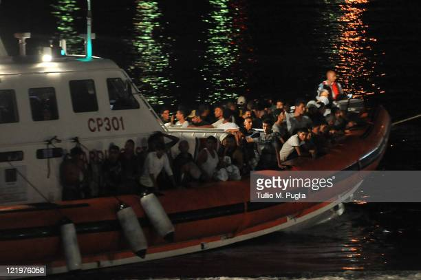 An Italian coastguard boat carrying migrants of an undetermined nationality sails into the island port on August 24 2011 in Lampedusa Italy Over...