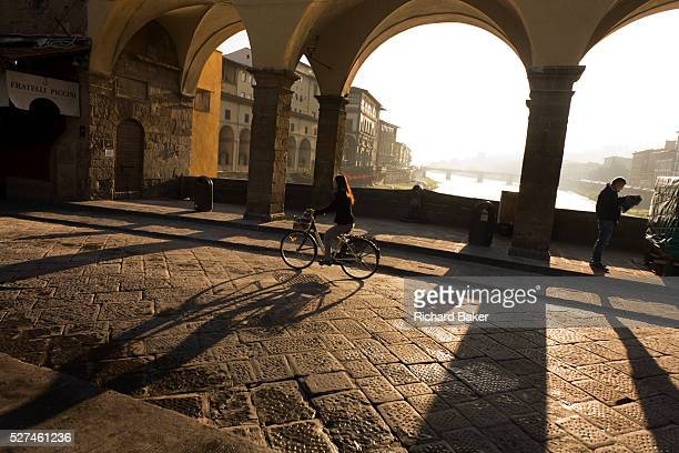 An Italian commuter cycles on her bike across the central arches of the Ponte Vecchio over the River Arno in Florence It is early on an autumnal...