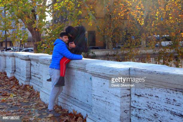 An Italian couple embraces on the Umberto I bridge over the River Tiber on a warm Autumn day on December 9 2017 in Rome Italy Despite controversy...