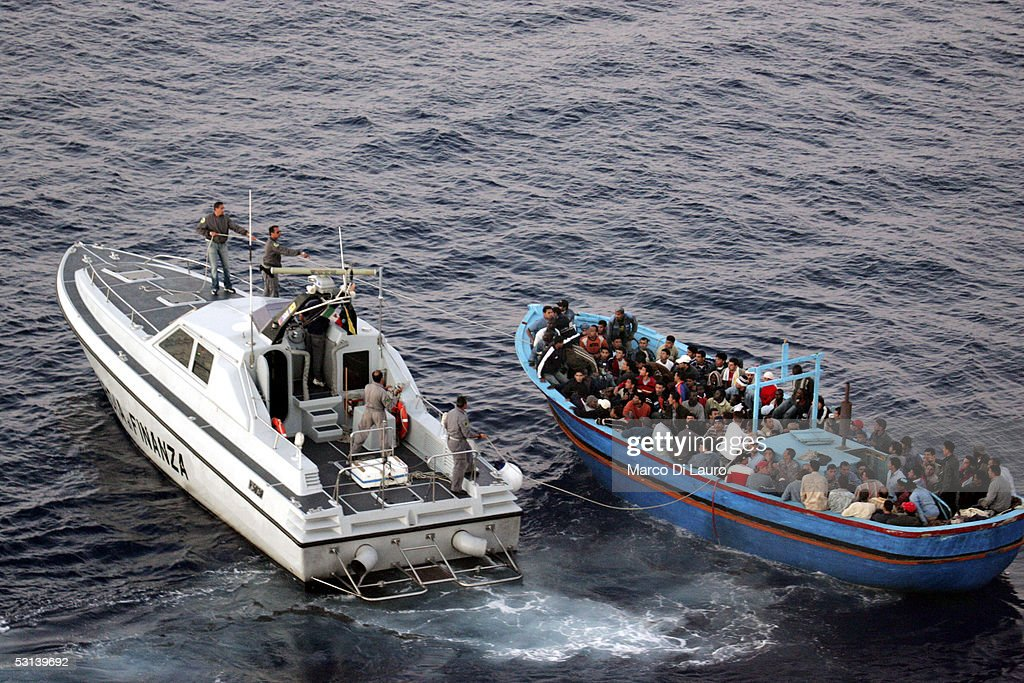 An Italian Custom Police 'Guardia di Finanza' boat approaches a boat loaded with illegal immigrants on June 21, 2005 in Lampedusa, Italy. Tens of thousands of immigrants land on the Italian coast each year, most of them heading from north Africa on ramshackle boats.In the Mediterranean Sea between Malta and Tunisia, Lampedusa Island is one of the main gateways for illegal immigration from Africa into Europe. According to a report by Amnesty International, Illegal immigrants who land in Italy consistently allege they have been abused, holding centres are overcrowded and no legal assistance is offered. Italian authorities refused to give access to the centres to enable further investigations by Amnesty. The Amnesty International report says 15,647 people were held in the centres in 2004: a 9 per-cent increase on the previous year.