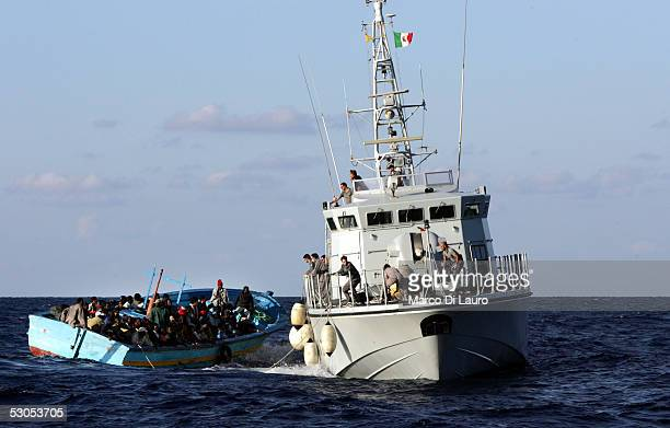 An Italian Customs Service boat prepares to take illegal immigrants on board June 10 2005 off the coast of Lampedusa Italy Lampedusa Island in the...
