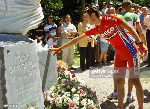 An Italian cyclist touches Fabio Casartelli's monument in the Col d'Aspet where the cyclist died in 1995 during the 11th stage of the 85th Tour de...