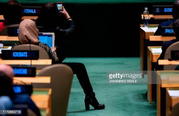 An Italian delegation member takes pictures of Prime Minister of Italy Giuseppe Conte as he speaks during the 74th session of the United Nations...