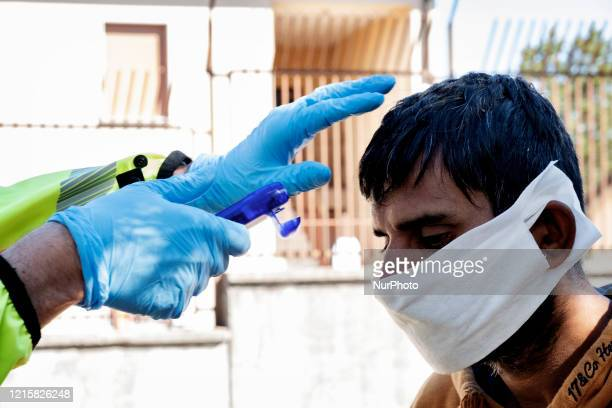 An Italian doctor of 118 check the temperature of a migrant in the police station of the Italian border town Fernetti to prevent the spread out of...