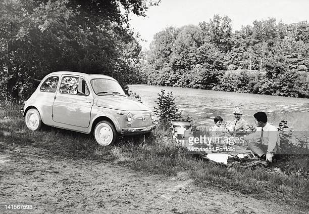 An Italian family picnicking by the riverside and her Fiat 500 Italy July 1957