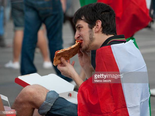 An Italian fan wearing Italy national flag eats a pizza in Piazza del Duomo while watching the football match on the maxi screen on June 14 2010 in...