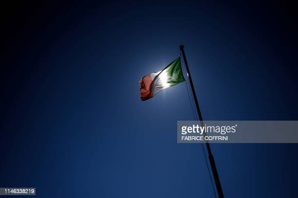 An Italian flag floats in the wind in Campione d'Italia a tiny Italian enclave on the shores of Switzerland's Lake Lugano on May 6 2019 Campione...