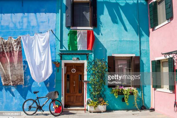 An Italian flag on a window in Burano island, part of the Venice Lagoon during the Covid19 Emergency.