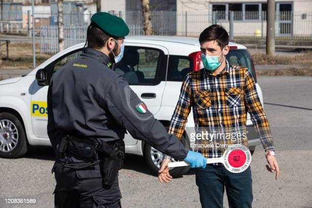 An Italian Guardia di Finanza officer, wearing a respiratory mask, talks to a young man at a road block on February 24, 2020 in Casalpusterlengo,...