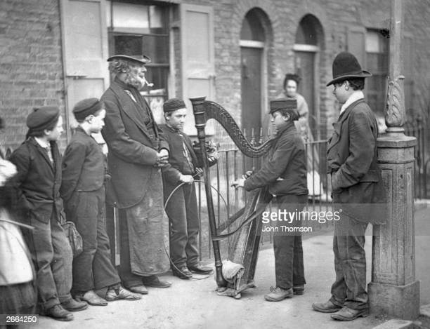 An Italian harpist entertaining local children on the street. Original Artwork: From 'Street Life In London' by John Thomson and Adolphe Smith