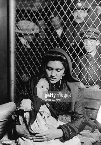 An Italian immigrant looks down at her daughter who is sitting on her lap upon their arrival at Ellis Island New York City They are both wearing...