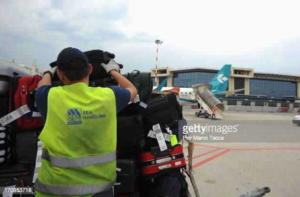 An Italian labourer loads luggage at Malpensa airport on June 20 2013 in Milan Italy Malpensa is one of the main international European airports with...