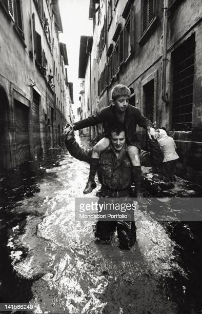 An Italian man carrying a child on his shoulders in a street inundated by the flood Florence November 1966