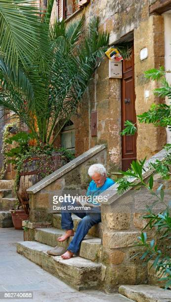 An Italian man reads outside his home on July 22 2015 in the medieval village of Pitigliano in the Grosseto province of Tuscany Italy Tuscany is...