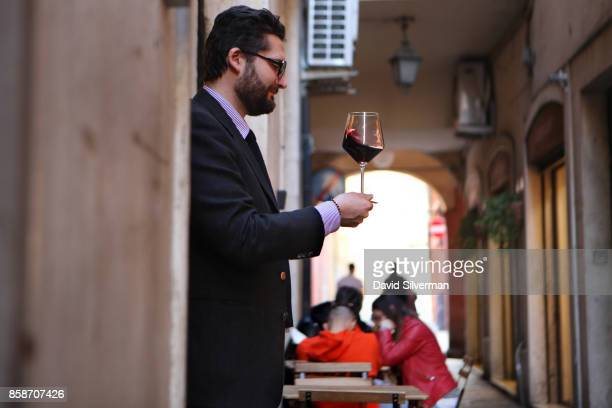An Italian man swirls his glass of wine in the doorway of the Ristretto Wine Bar on March 28 2017 in Modena in the Italian province of EmiliaRomagna...