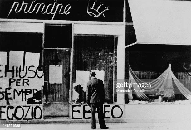 An Italian man watching the antiSemitic graffiti and broken windows of a Jewish store picked on by Fascists Trieste 1942