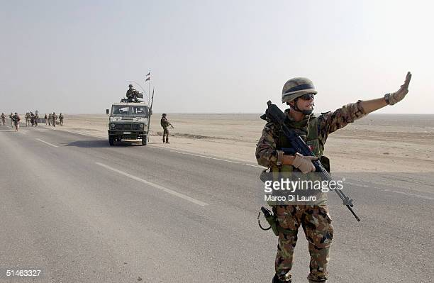 An Italian marine from the Italian Joint Task Force Iraq, San Marco Regiment, holds up a vehicle at a check point on the Tampa road from Basrah to...