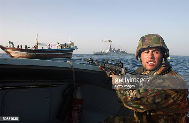 An Italian Marine from the Italian Maestrale class frigate ITS Scirocco sets security for the remainder of his team to safely board a local cargo...