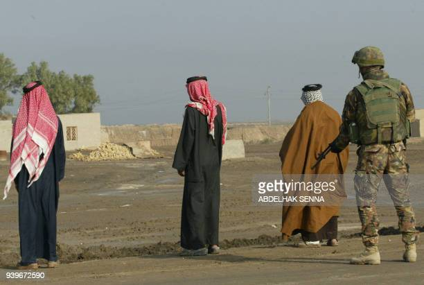 An Italian marine from the San Marco regiment guards three Iraqi tribesmen during a security check near the US military base of Talil near the...